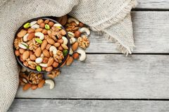 Wooden bowl with nuts on a wooden background, near a bag from burlap. Healthy food and snack, organic vegetarian food. Walnut, pistachios, almonds, hazelnuts stock photo