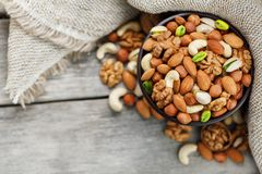 Wooden bowl with nuts on a wooden background, near a bag from burlap. Healthy food and snack, organic vegetarian food. Walnut, pistachios, almonds, hazelnuts stock image