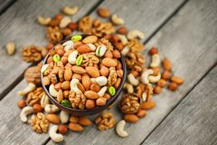 Wooden bowl with nuts on a wooden background, near a bag from burlap. Healthy food and snack, organic vegetarian food. Walnut, pistachios, almonds, hazelnuts royalty free stock photos