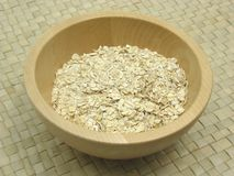 Wooden bowl with oat flakes. On rattan underlay Royalty Free Stock Photo