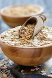 Wooden bowl with oat flakes and whole grain scoop. Wooden bowl with oat flakes and the scoop on an old table, selective focus Stock Images