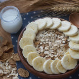 Wooden bowl of organic cornflakes and oatmeal with banana. Nutritious breakfast, raw food ingredients Stock Photography