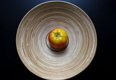 Wooden bowl. Original wooden plate with continuous lines and one apple on the black table. Organic, natural material of bowl with eternal lines. Eco-friendly royalty free stock photography