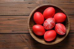 Wooden bowl with painted red Easter eggs on table, top view. Space for text royalty free stock image