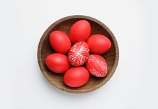 Wooden bowl with painted red Easter eggs on white background. Top view royalty free stock photography