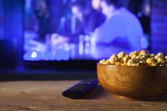 A wooden bowl of popcorn and remote control in the background the TV works. Evening cozy watching a movie or TV series at home. A wooden bowl of popcorn and the Stock Image