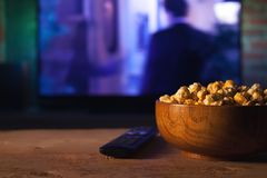 A wooden bowl of popcorn and remote control in the background the TV works. Evening cozy watching a movie or TV series at home. A wooden bowl of popcorn and the Royalty Free Stock Images