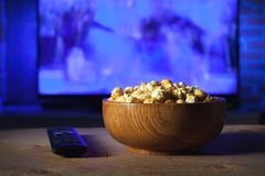 A wooden bowl of popcorn and remote control in the background the TV works. Evening cozy watching a movie or TV series at home. A wooden bowl of popcorn and the Stock Photography