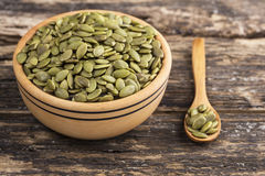 Wooden bowl and pumpkin seeds Stock Images