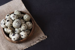 Wooden bowl with quail eggs. Dark food photography. Rustic background, selective focus and diffused natural light. Royalty Free Stock Images