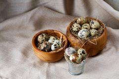 Bowl with eggs quail, eggs on a homespun napkin on grey background, close-up, selective focus. Wooden bowl with quail eggs, eggs on a homespun napkin on grey Royalty Free Stock Photos