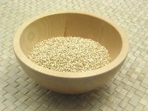 Wooden bowl with quinoa. On rattan underlay Royalty Free Stock Photo