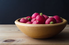 Wooden Bowl of Radishes on Black Background. A wooden bowl of  fresh red radishes on plank wood table with black chalkboard background Stock Photography