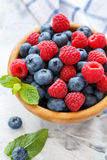 Wooden bowl with raspberries and blueberries. Stock Image