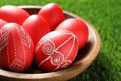 Wooden bowl with red painted Easter eggs on grass, closeup. Wooden bowl with red painted Easter eggs on green grass, closeup royalty free stock photography