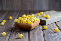 Wooden bowl of ripe gooseberry yellow. On a wooden background Royalty Free Stock Images