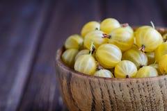 Wooden bowl of ripe gooseberry yellow. Macro Stock Photography