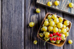 Wooden bowl of ripe gooseberry yellow with red currant. Top view, copyspace Stock Photos