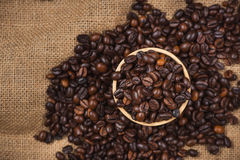 Wooden bowl with roasted coffee beans on rustic background. Royalty Free Stock Image