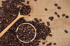 Wooden bowl with roasted coffee beans on rustic background. Stock Image