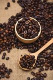 Wooden bowl with roasted coffee beans on rustic background. Stock Images