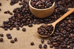 Wooden bowl with roasted coffee beans on rustic background. Royalty Free Stock Photography
