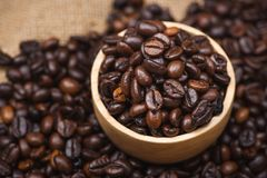 Wooden bowl with roasted coffee beans on rustic background. Wooden bowl with roasted coffee beans on rustic background Royalty Free Stock Photos
