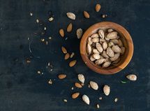 Wooden bowl of salty almond nuts in nutshell Royalty Free Stock Photo