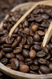 Wooden bowl and scoop with coffee beans, selective focus Stock Photos