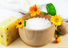 Wooden bowl with sea salt, soap, towels and marigolds. Composition from wooden bowl with sea salt, soap, towels and marigolds on the mat Stock Image