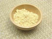 Wooden bowl with soy meal. On rattan underlay Royalty Free Stock Images