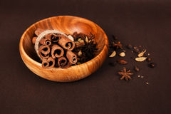 Wooden bowl with spices. Ror mulled wine on brown background Stock Image