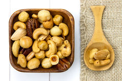 Wooden bowl and spoon filled with nuts Stock Image