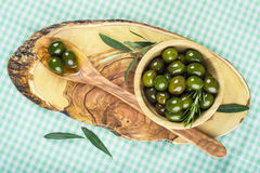 Wooden bowl and spoon with green olives and olive oil Stock Photo