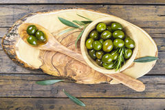 Wooden bowl and spoon with green olives and olive oil Stock Photos