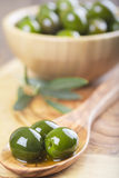 Wooden bowl and spoon with green olives and olive oil Royalty Free Stock Photography