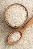 Wooden bowl and spoon with parboiled rice on background of scattered rice. Stock Photography