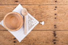Wooden bowl, spoon and tablecloth on a rustic wooden table. Wooden bowl, spoon and tablecloth on an old rustic wooden table - copy space Stock Photo
