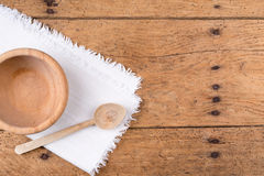 Wooden bowl, spoon and tablecloth on a rustic wooden table Stock Images
