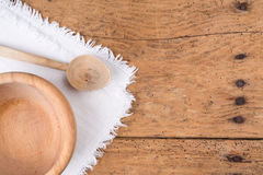 Wooden bowl, spoon and tablecloth on a rustic wooden table. Wooden bowl, spoon and tablecloth on an old rustic wooden table - copy space Royalty Free Stock Images