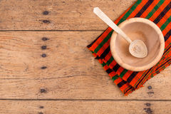Wooden bowl, spoon and tablecloth on a rustic wooden table. Wooden bowl, spoon and tablecloth on an old rustic wooden table - copy space Royalty Free Stock Photography
