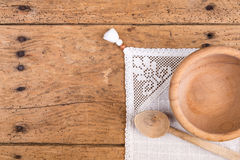 Wooden bowl, spoon and tablecloth on a rustic wooden table. Wooden bowl, spoon and tablecloth on an old rustic wooden table - copy space Royalty Free Stock Photo