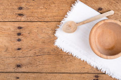 Wooden bowl, spoon and tablecloth on a rustic wooden table Royalty Free Stock Images