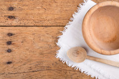 Wooden bowl, spoon and tablecloth on a rustic wooden table Royalty Free Stock Photo