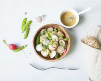 A wooden bowl of spring vegetable salad with mustard dressing on Stock Photos