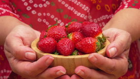 Wooden bowl of strawberries in hands stock video footage