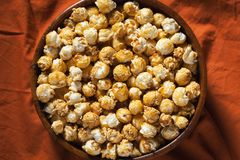 Wooden bowl with sweet popcorn on orange bedding. Snacks and food for a movie. Top view with copy space royalty free stock image