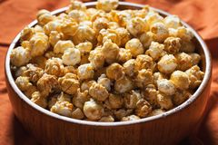 Wooden bowl with sweet popcorn on orange bedding. Snacks and food for a movie.  Stock Photo