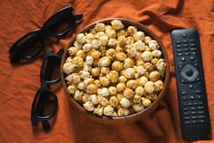 Wooden bowl with sweet popcorn, TV remote control and 3D glasses on orange bedding. Top view. Snacks and food for a movie stock photography