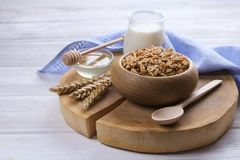 A wooden bowl of trail mix with almonds, raisins, seeds, cashew, hazelnut nuts, glass of milk and honey on white table. Vegetarian. Dietary sports nutrition Royalty Free Stock Photos